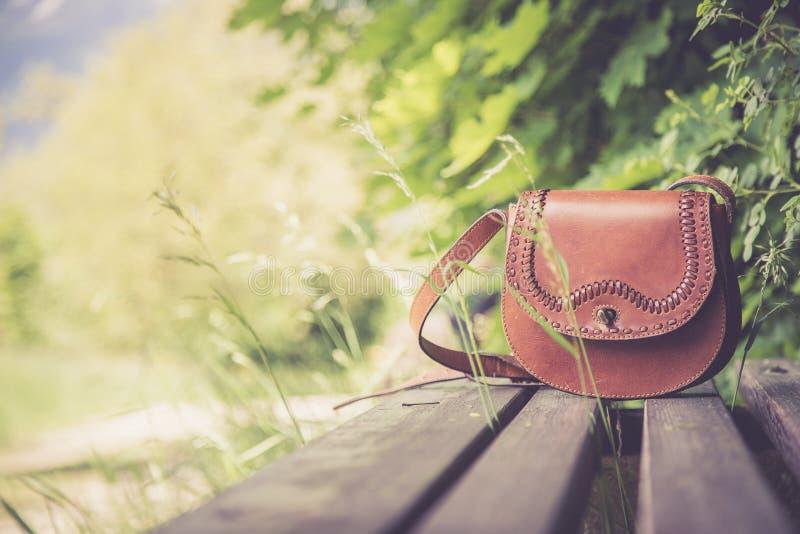 Ξεχασμένη τσάντα δέρματος σε έναν πάγκο πάρκων, κανένας στοκ φωτογραφία