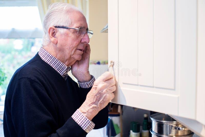 Ξεχασμένος Ανώτερος Άνδρας Με Άνοια Που Κοιτάζει Στο Ντουλάπι Στο Σπίτι στοκ εικόνες