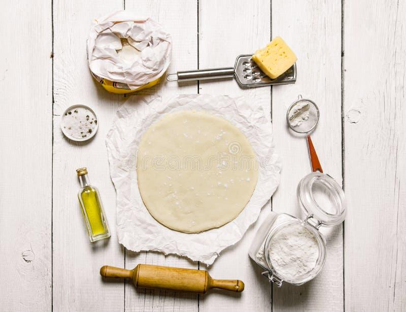 Ξεδιπλώστε τη ζύμη και τα συστατικά πιτσών - αλεύρι, τυρί, olivkovoe πετρέλαιο στοκ εικόνα με δικαίωμα ελεύθερης χρήσης