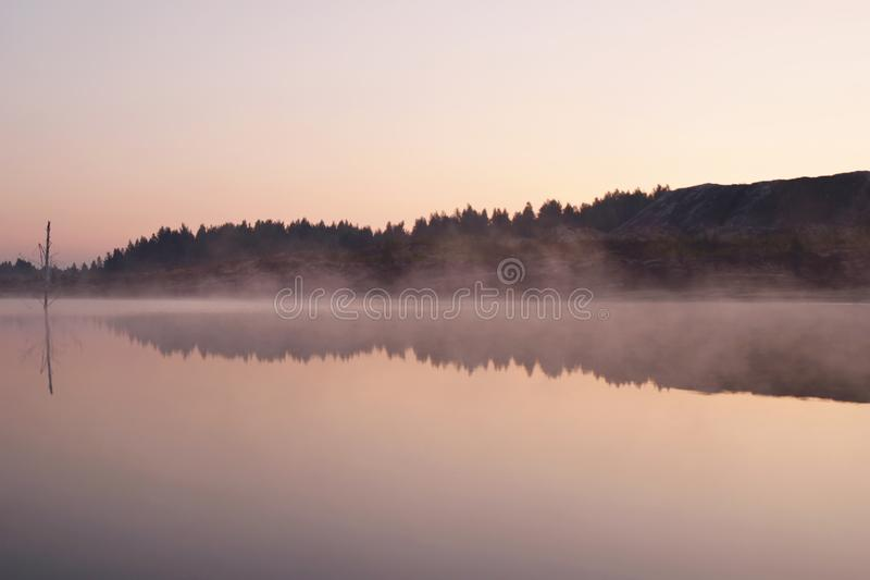 Ξημερώματα τοπίων στη λίμνη με την ομίχλη και την αντανάκλαση του δάσους και τους λόφους σε ένα νερό στοκ φωτογραφία με δικαίωμα ελεύθερης χρήσης