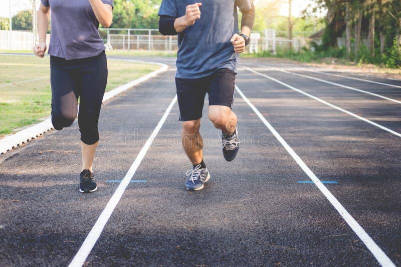 Ξημερώματα workout, τέντωμα ζευγών ικανότητας υπαίθρια στο πάρκο Νεαρός άνδρας και γυναίκα που ασκούν μαζί το πρωί, διαβίωση στοκ φωτογραφία