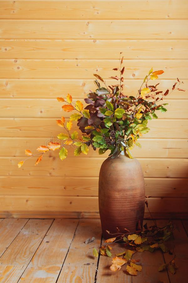 Ξηρά ανθοδέσμη φθινοπώρου στο κεραμικό βάζο στο ξύλινο υπόβαθρο στοκ φωτογραφίες