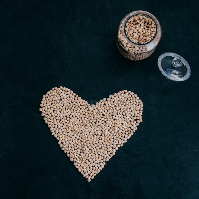 Ξηρά καθαρά chickpeas στο βάζο γυαλιού Καρδιά φιαγμένη από οργανικό άψητο garbanzo   Βασισμένη στις εγκαταστάσεις πρωτεΐνη Φασόλι στοκ φωτογραφία με δικαίωμα ελεύθερης χρήσης
