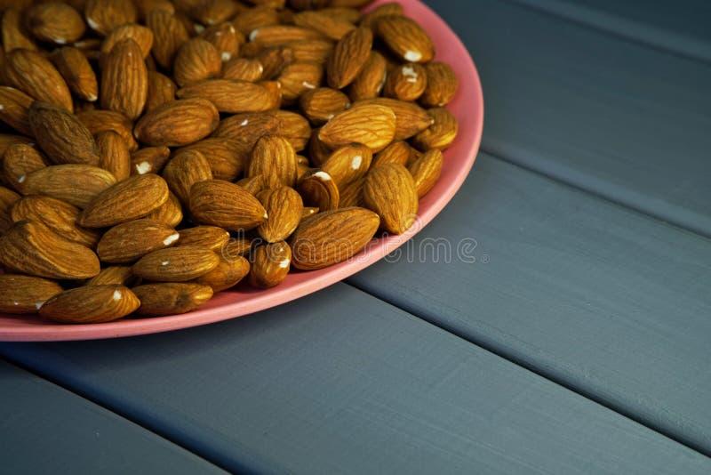 Ξηρά καρύδια αμυγδάλων σε ένα ρόδινο πιάτο σε ένα ξύλινο υπόβαθρο στοκ φωτογραφίες με δικαίωμα ελεύθερης χρήσης