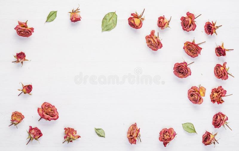 Ξηρά λουλούδια τριαντάφυλλων στον εκλεκτής ποιότητας ξύλινο πίνακα στοκ φωτογραφία