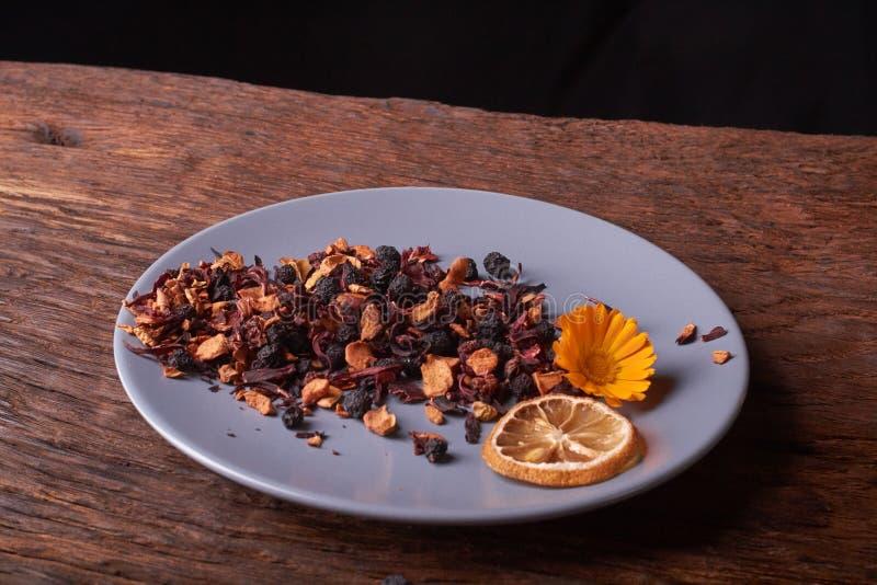 ξηρά λουλούδι και λεμόνι τσαγιού φρούτων στο πιάτο Κόκκινος ξύλινος πίνακας της Νίκαιας Έννοια της υγιεινής διατροφής στοκ φωτογραφίες