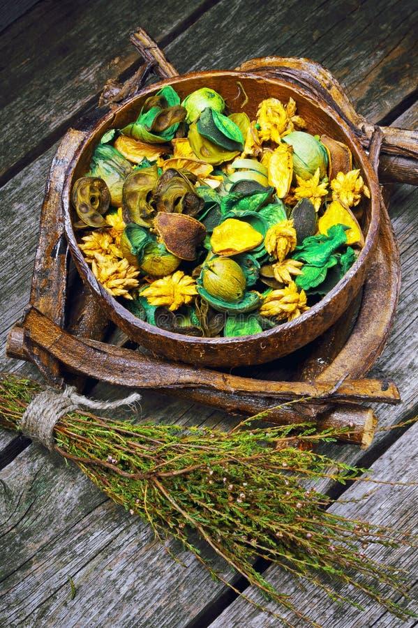 Ξηρά λουλούδια σε ένα ξύλινες κύπελλο και μια ερείκη σε ένα ξύλινο υπόβαθρο στοκ φωτογραφίες