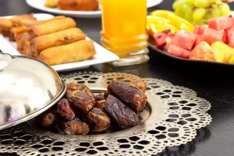 Ξηρά φρούτα φοινικών ημερομηνιών, φρέσκος χυμός από πορτοκάλι, πρόχειρο φαγητό samosa και έννοια υποβάθρου φρούτων iftar στον ιερ στοκ εικόνες