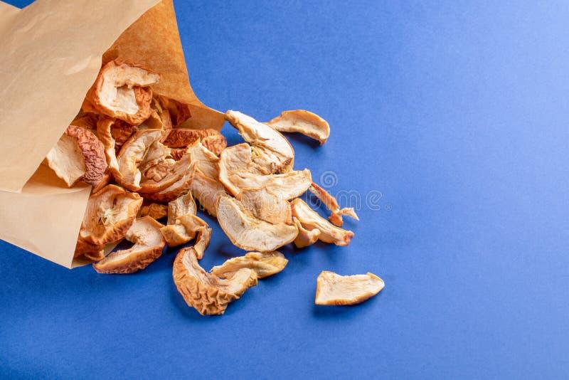 Ξηρές φέτες μήλων που διασκορπίζονται από την τσάντα εγγράφου στο μπλε υπόβαθρο στοκ φωτογραφία με δικαίωμα ελεύθερης χρήσης