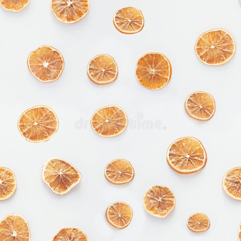 Ξηρές φέτες των πορτοκαλιών στο άσπρο άνευ ραφής σχέδιο υποβάθρου στοκ εικόνες