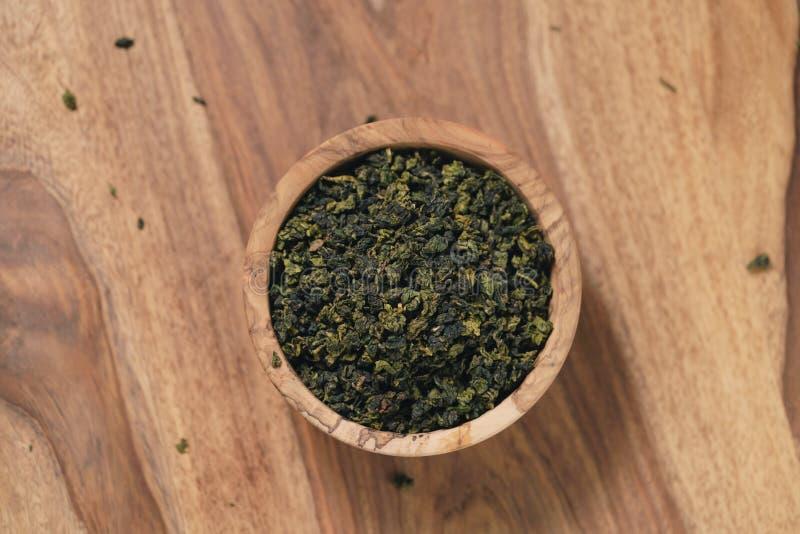 Ξηρό οργανικό πράσινο τσάι oolong στο ξύλινο κύπελλο στοκ φωτογραφία με δικαίωμα ελεύθερης χρήσης