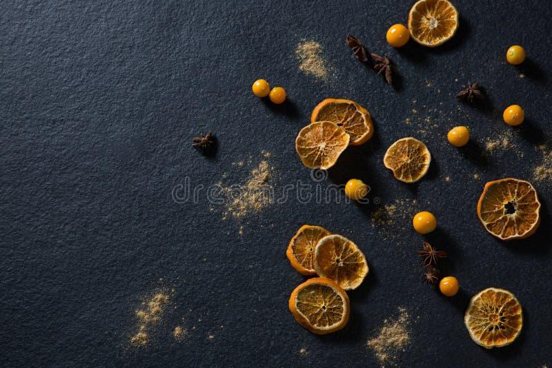 Ξηρό πορτοκάλι με το γλυκάνισο αστεριών και χρυσά μούρα στο μαύρο υπόβαθρο ελεύθερη απεικόνιση δικαιώματος