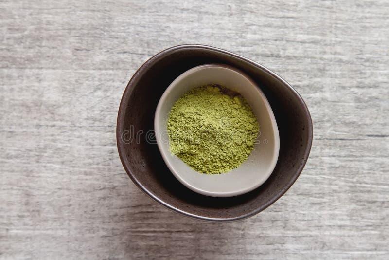 Ξηρό τσάι Matcha σε ένα μικρό καφετί πιάτο Γκρίζο ξύλινο υπόβαθρο κορυφή στοκ φωτογραφία με δικαίωμα ελεύθερης χρήσης