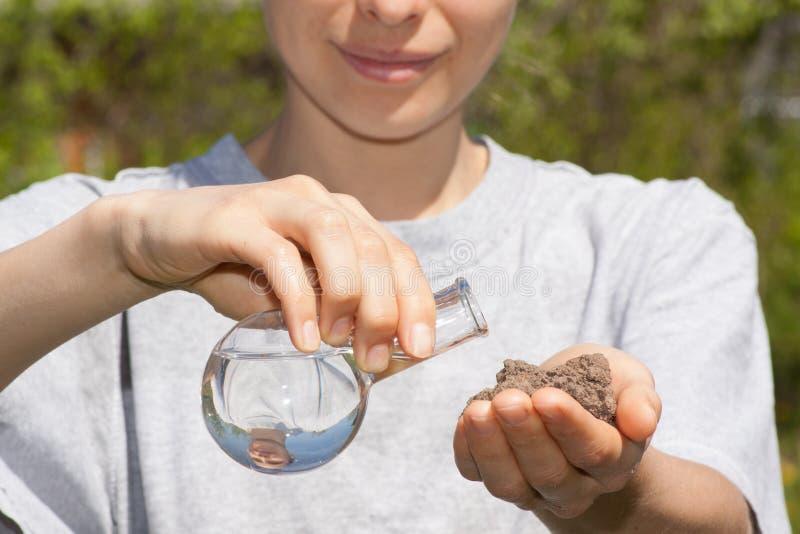 Ξηρό χώμα υπό εξέταση και μια φιάλη με το νερό στοκ εικόνες