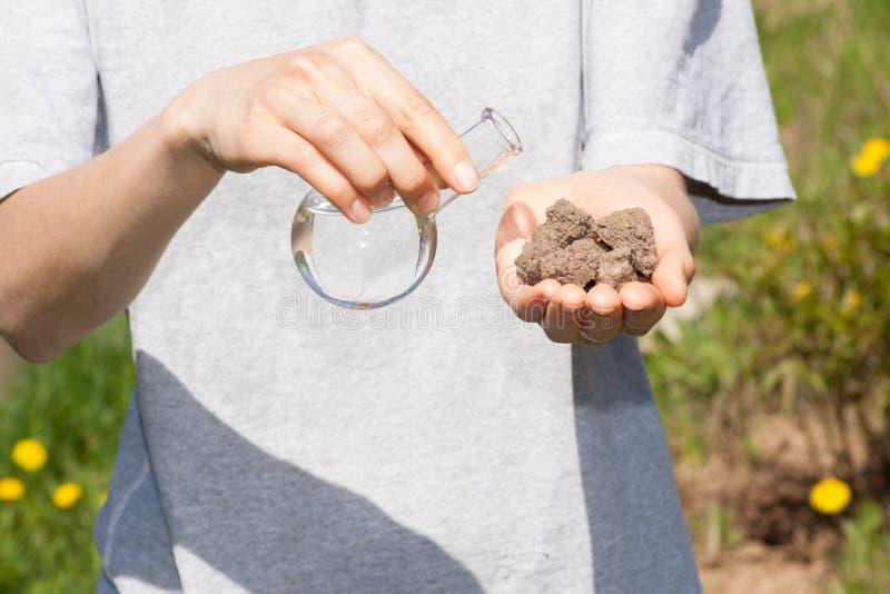 Ξηρό χώμα υπό εξέταση και μια φιάλη με το νερό στοκ φωτογραφία με δικαίωμα ελεύθερης χρήσης