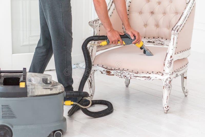 Ξηρό cleaner& x27 το χέρι υπαλλήλων του s καθαρίζει τον κλασσικό καναπέ με επαγγελματικά τη μέθοδο εξαγωγής στοκ φωτογραφίες
