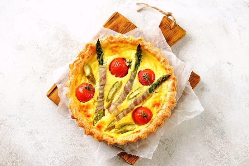 Ξινή πίτα με τις ντομάτες τυριών, σπαραγγιού, μπέϊκον και κερασιών r στοκ εικόνα