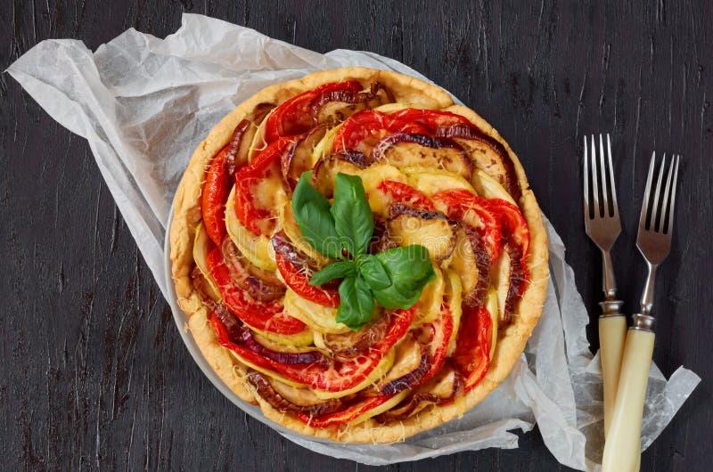 Ξινός με τις μελιτζάνες και τις ντομάτες που διακοσμούνται με φρέσκα φύλλα βασιλικού και δύο δίκρανα Σπιτική φυτική πίτα στο μαύρ στοκ εικόνες