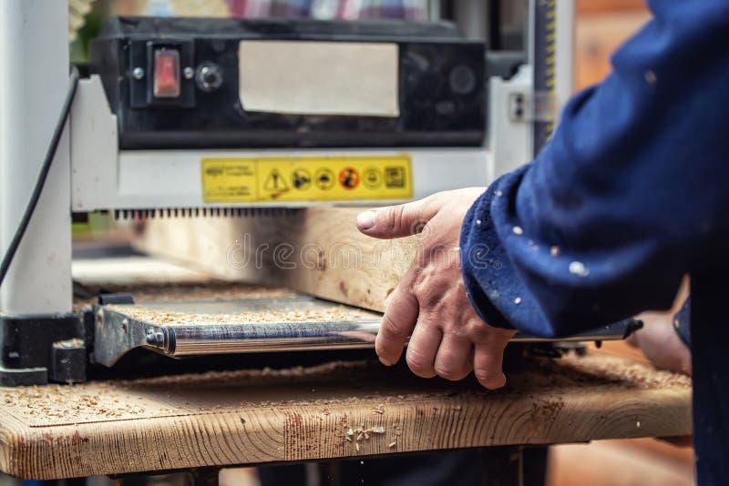 Ξυλουργική βιοτεχνών στην ξυλουργική με τα μέρη των σύγχρονων επαγγελματικών εργαλείων δύναμης Άτομο που χρησιμοποιεί τη thicknes στοκ εικόνα