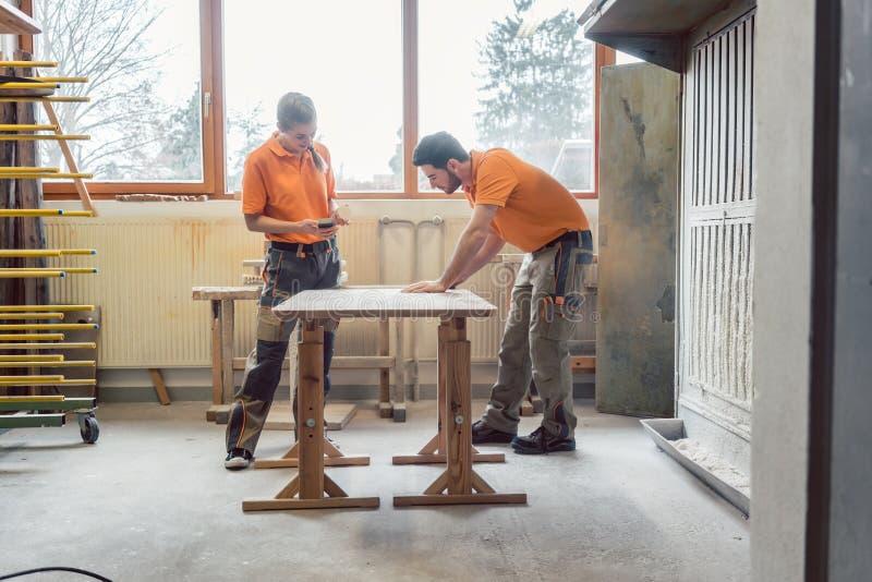Ξυλουργοί ομάδας wo συχνά που εργάζονται σε έναν πίνακα στοκ φωτογραφία με δικαίωμα ελεύθερης χρήσης