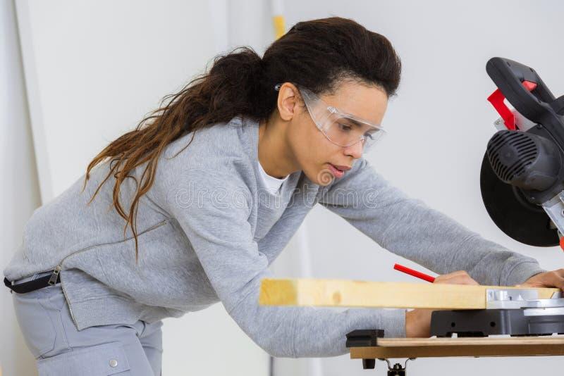 Ξυλουργός κοριτσιών που χρησιμοποιεί το κυκλικό πριόνι στοκ εικόνες με δικαίωμα ελεύθερης χρήσης
