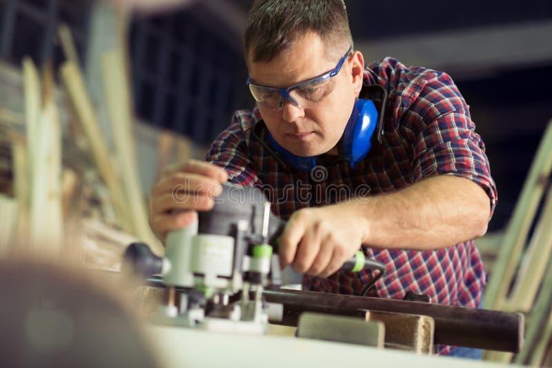 Ξυλουργός με έναν ηλεκτρικό δρομολογητή στοκ εικόνες με δικαίωμα ελεύθερης χρήσης