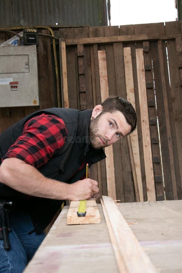 Ξυλουργός, ξύλινη εργασία εργαζομένων που μετρά, που τρυπά και που κάνει το προϊόν ξυλείας με τρυπάνι στοκ φωτογραφία με δικαίωμα ελεύθερης χρήσης