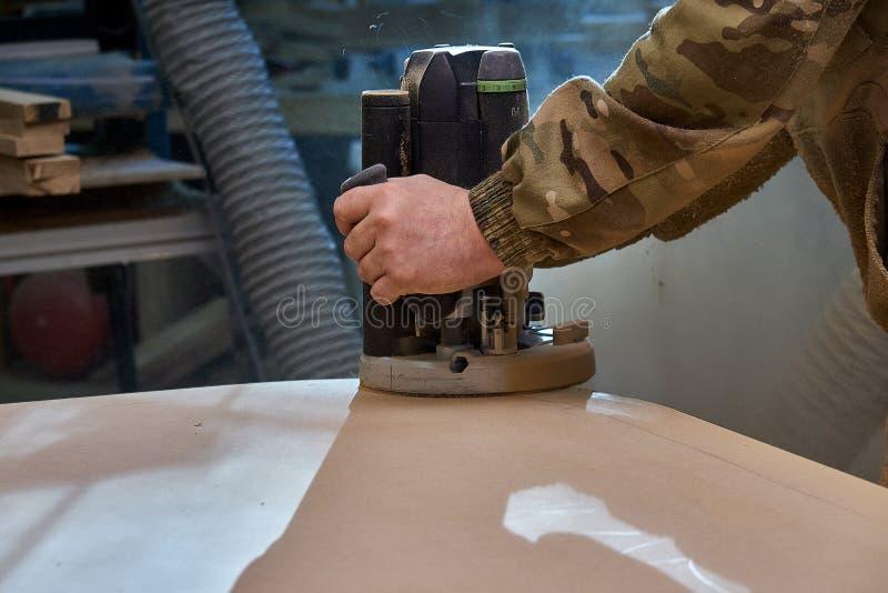 Ξυλουργός που εργάζεται με τη χειρωνακτική μηχανή άλεσης χεριών στο εργαστήριο Ξύλινη διαδικασία παραγωγής επίπλων στοκ εικόνες με δικαίωμα ελεύθερης χρήσης