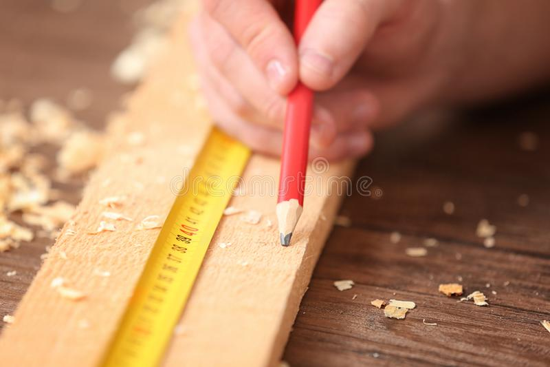 Ξυλουργός που εφαρμόζει το χαρακτηρισμό επάνω στον ξύλινο πίνακα ι στοκ εικόνες