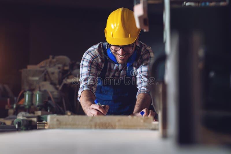 Ξυλουργός που μετρά σχετικά με έναν ξύλινο φραγμό που στέκεται σε έναν πίνακα σε ένα εργαστήριο στοκ εικόνες