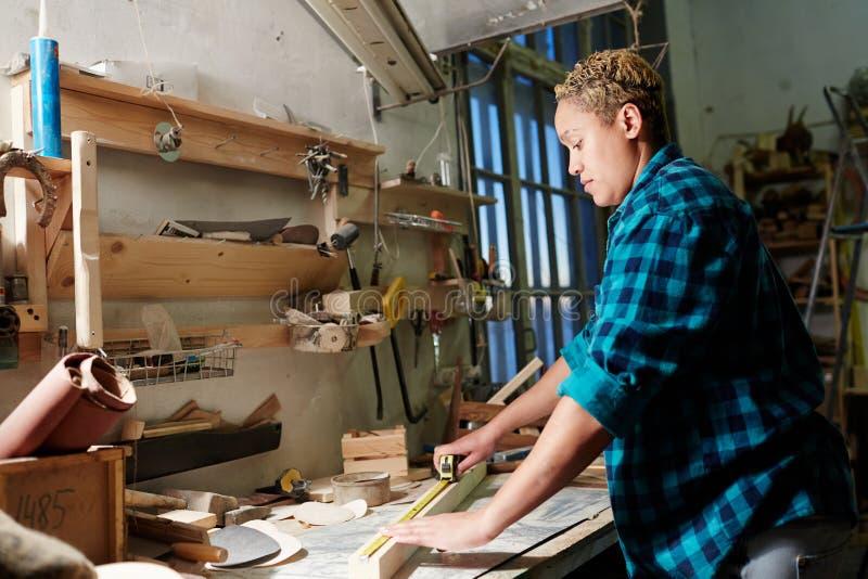 Ξυλουργός που μετρά την ξύλινη σανίδα στοκ φωτογραφίες