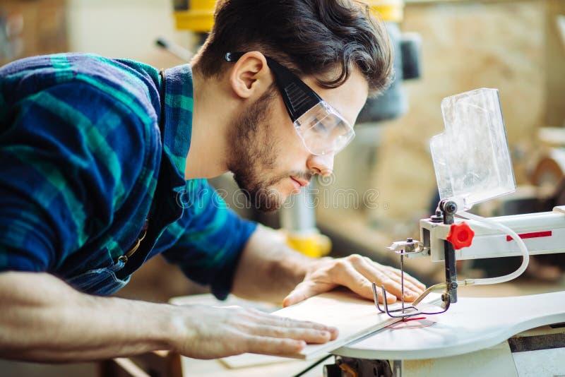 Ξυλουργός που συμμετέχεται στο ξύλο επεξεργασίας στο πριονιστήριο στοκ εικόνες