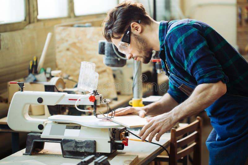 Ξυλουργός που συμμετέχεται στο ξύλο επεξεργασίας στο πριονιστήριο στοκ εικόνες με δικαίωμα ελεύθερης χρήσης