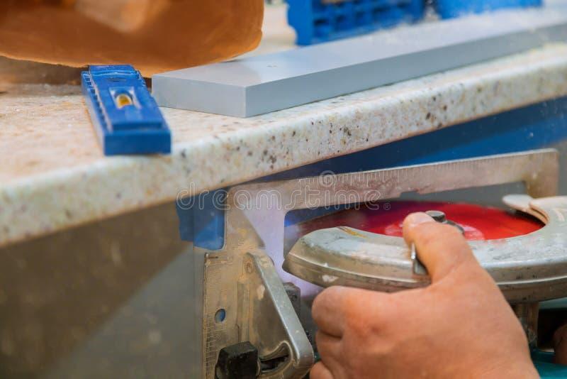 Ξυλουργός που χρησιμοποιεί το κυκλικό πριόνι για την κοπή των ξύλινων πινάκων με τα εργαλεία δύναμης χεριών στοκ εικόνες
