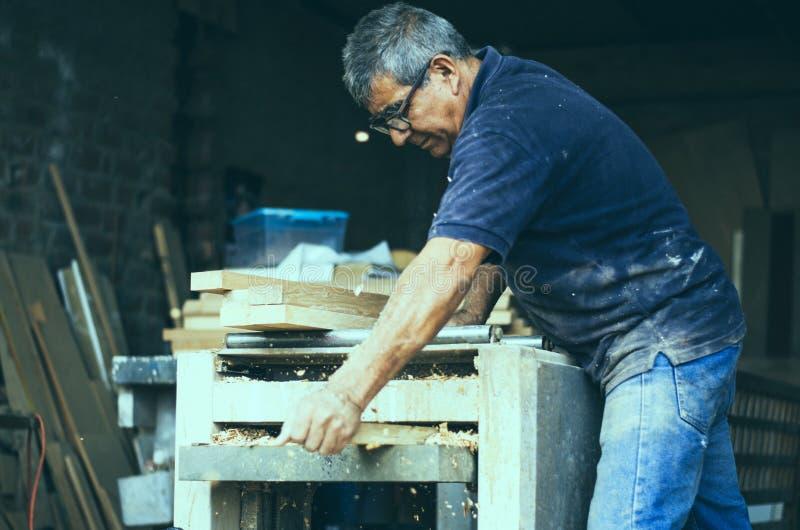Ξυλουργός που χρησιμοποιεί sander ζωνών Ξυλουργός που στρώνει με άμμο ένα ξύλο στοκ εικόνες