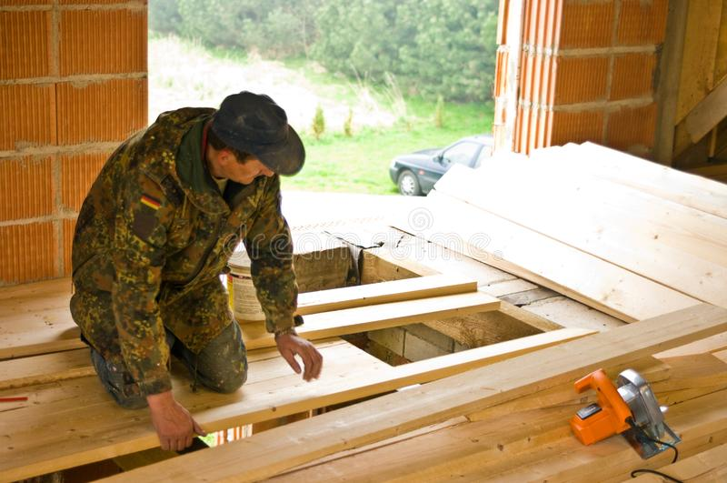 Ξυλουργός που χτίζει το νέο πάτωμα ενός δωματίου σοφιτών στοκ φωτογραφία με δικαίωμα ελεύθερης χρήσης