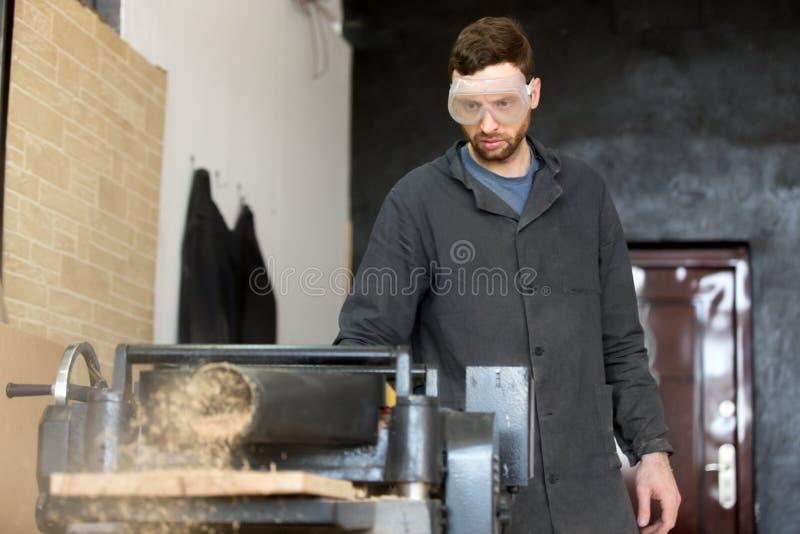 Ξυλουργός στα εργοστάσια γυαλιών ασφάλειας για την εργαλειομηχανή στοκ εικόνες με δικαίωμα ελεύθερης χρήσης