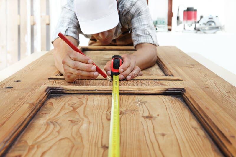 Ξυλουργός στα μέτρα εργασίας με το μέτρο ταινιών και μολύβι στο W στοκ φωτογραφίες