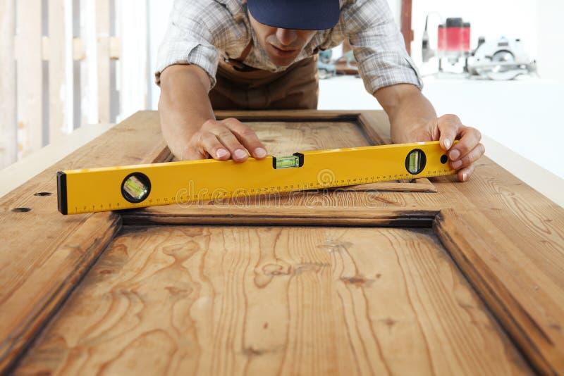 Ξυλουργός στην εργασία με το επίπεδο πνευμάτων στο ξύλινο υπόβαθρο στοκ φωτογραφία