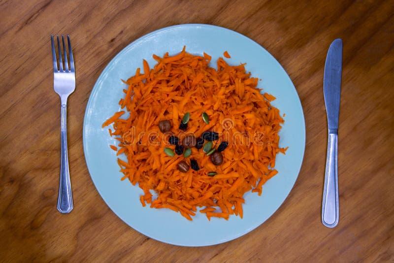 Ξυμένα καρότο, σταφίδα και καρύδι στο πιάτο που εξυπηρετείται για τα τρόφιμα Υγιεινή διατροφή στον ξύλινο πίνακα Κοκκιώδες καρότο στοκ φωτογραφία με δικαίωμα ελεύθερης χρήσης