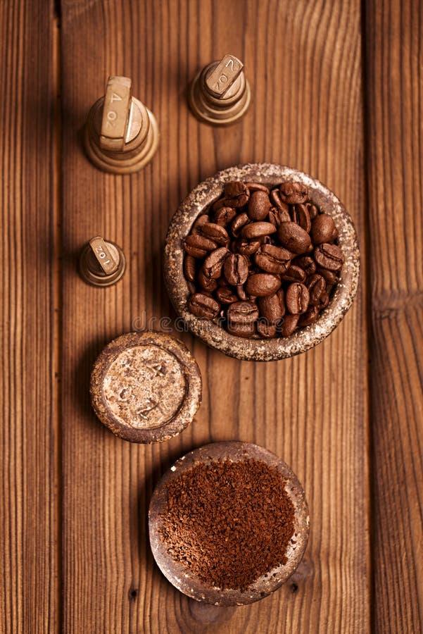 Ξυμένος καφές σε παλαιά βάρη σιδήρου και το ξύλινο υπόβαθρο στοκ φωτογραφίες