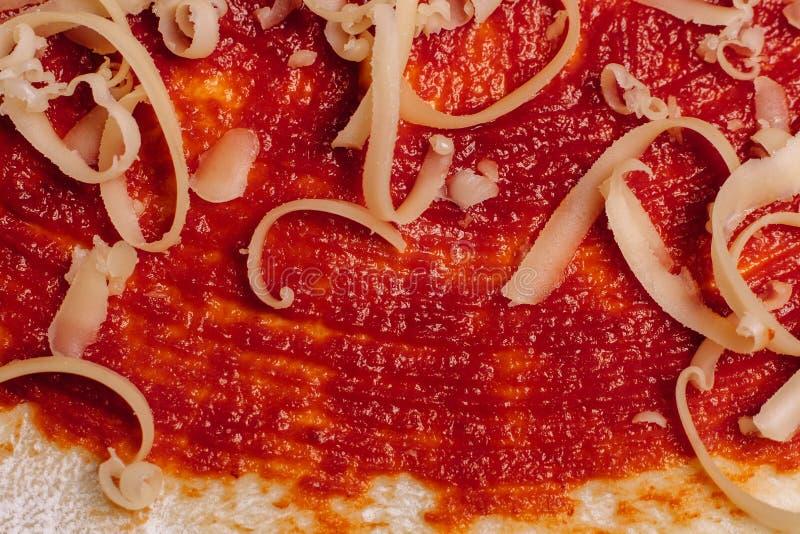 Ξυμένο τυρί για την πίτσα κοντά επάνω ντυμένη στην κέτσαπ ζύμη στοκ φωτογραφίες