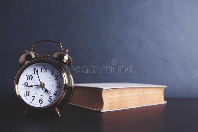 Ξυπνητήρι ένα βιβλίο στοκ φωτογραφίες