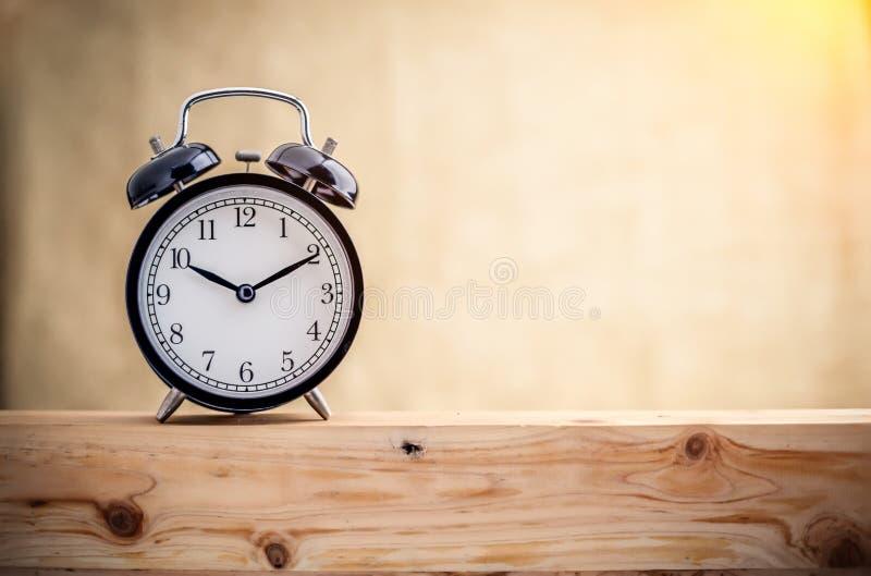 Ξυπνητήρι σε ένα ξύλινο πιάτο στοκ εικόνα