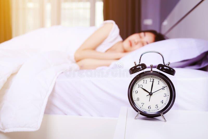 Ξυπνητήρι στον ύπνο πινάκων και γυναικών στο κρεβάτι στην κρεβατοκάμαρα στοκ εικόνες