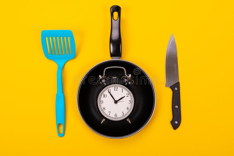 Ξυπνητήρι στο τηγάνι και φτυάρι που απομονώνεται έπειτα στο κίτρινο υπόβαθρο στοκ εικόνα με δικαίωμα ελεύθερης χρήσης
