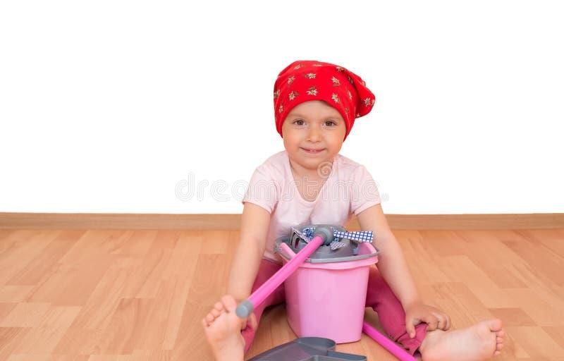 Ξυπόλυτο μικρό κορίτσι με τη συνεδρίαση εξοπλισμού καθαρισμού παιχνιδιών στο πάτωμα που απομονώνεται στοκ φωτογραφία με δικαίωμα ελεύθερης χρήσης