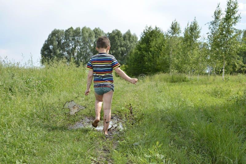 Ξυπόλυτα τρεξίματα αγοριών μέσω μιας λακκούβας στοκ εικόνα με δικαίωμα ελεύθερης χρήσης
