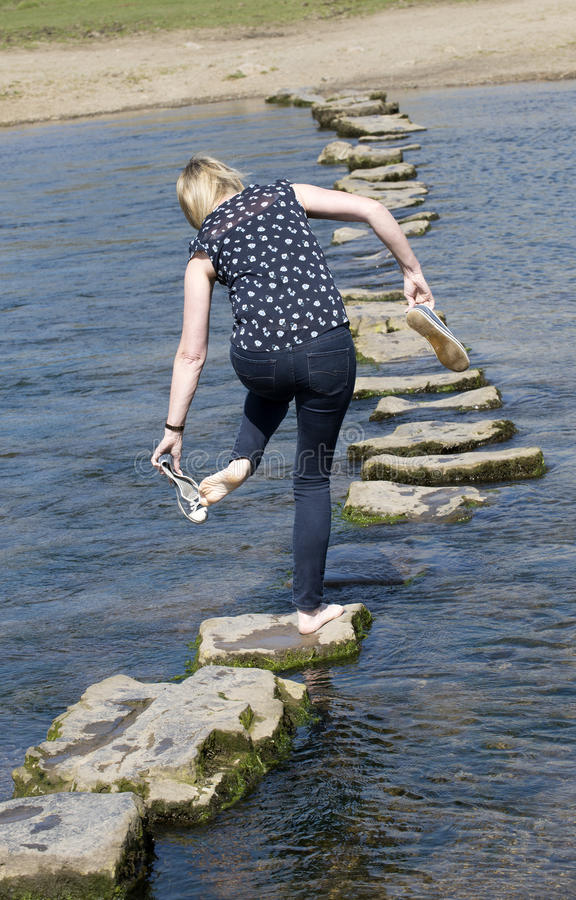 Ξυπόλυτο περπάτημα γυναικών περπατώντας πετρών απέναντι στοκ φωτογραφία