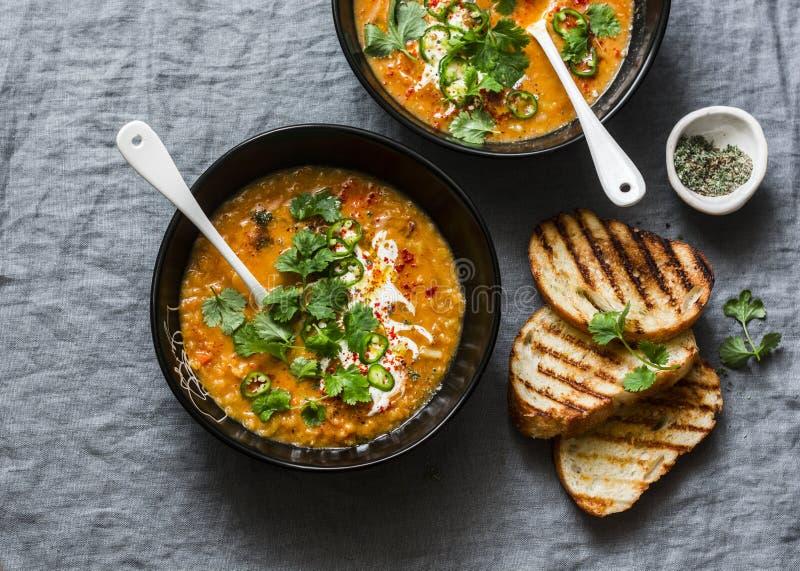 Ξυστρισμένες κόκκινες ντομάτα φακών και σούπα καρύδων - εύγευστα χορτοφάγα τρόφιμα στο γκρίζο υπόβαθρο, τοπ άποψη Επίπεδος βάλτε στοκ εικόνες